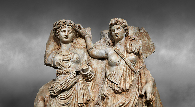 Close up of a Roman Sebasteion relief  sculpture of Aphrodite crowned by Andreia, Aphrodisias Museum, Aphrodisias, Turkey.  Against a grey background.<br /> <br /> A draped goddess is crowned by a female warrior figure. The goddess is probably Aphrodite, while the warrior has a bare breated Amazonian dress and equipment (spear, sword strap and shield) worn by Roma or Andreia (Bravery)