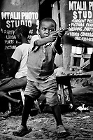 A boy playing with a toy gun in Kibera.