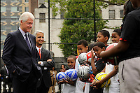 Former President Bill Clinton talks with students prior to a press conference announcing former President Bill Clinton as the honorary chairman of the USA Bid Committee to host the FIFIA World Cup in 2018 or 2022 at the FC Harlem Field in Harlem, NY, on May 17, 2010.