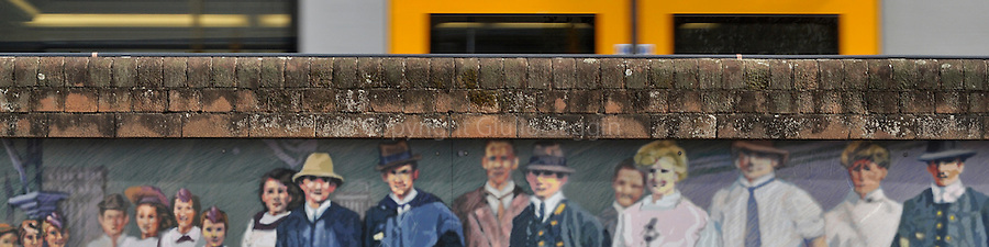 A train leaves Central Station in the Sydney CBD as the faces of characters in a mural painted on a wall of the station stare out onto Elizabeth Street.