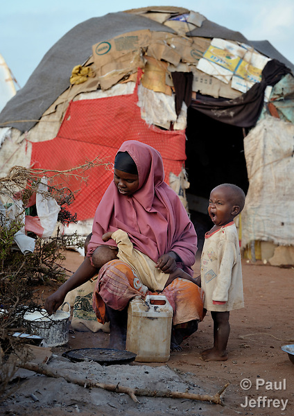 Kadija Abdi Wadadow nurses one child while her son Bashir Aliyon yawns in the Dadaab refugee complex in northeastern Kenya. Fleeing violence and drought, hundreds of thousands of Somali refugees have made Dadaab the largest refugee settlement in the world.