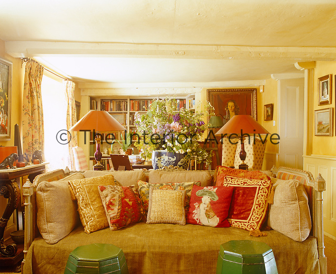 Low ceilings and a colour scheme of yellow, gold and red have resulted in a living room of cosy charm
