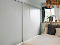 Sliding wardrobe doors keep space clear in the master bedroom. The headboard is made from the walls of the torn down garden shed