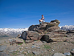 Woman sitting on rocky outcrop in the Sierra Nevada Mountains in the High Alpujarras, near Capileira, Granada Province, Spain