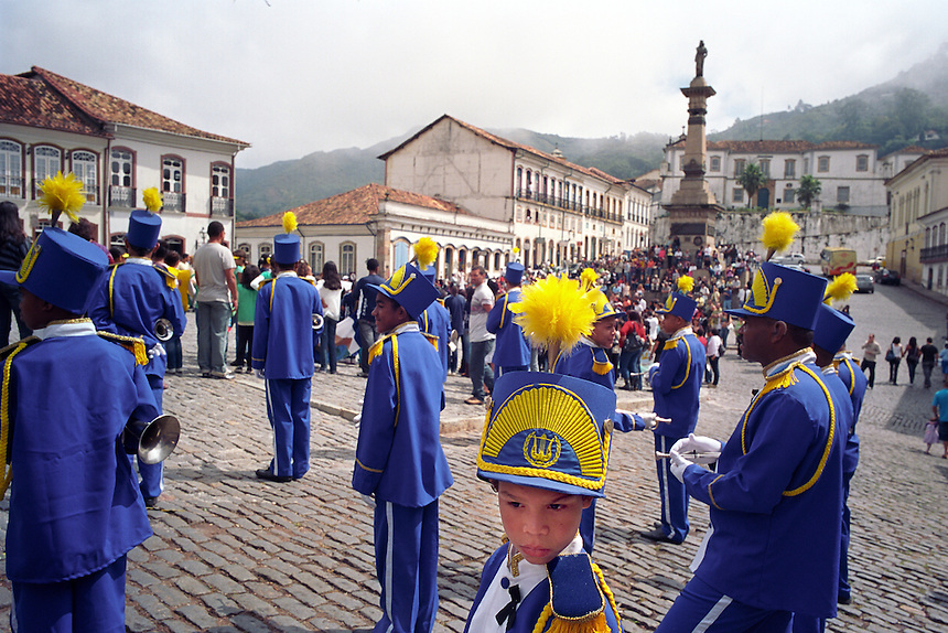 Musicians from a number of local marching bands perform in the central square of Ouro Preto (circumflex over the e in Preto), Brazil, in celebration of the country's 1822 independence from Portugal. The city was the center of a 1789 republican conspiracy, the leader of which was beheaded. His head was displayed on a pike where the momument at rear now stands. Brazil's interior state of Minas Gerais, once a colonial mining capitol for the Portuguese crown, has changed little in appearance since the 18th century. With the help of laws to preserve its baroque architecture, the state's sky is scraped at every turn by 250-year-old church steeples, and lined with cobblestones. (Kevin Moloney for the New York Times)