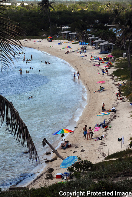 view from above of Caloosa Beach at Bahia Honda State Park in the Florida Keys.  Bright colored sun umbrellas on sand, bathers in water