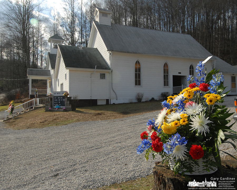 Flower arrangements sit on a stump at the Sago Baptist church near Buckhannon, WV, Monday, Jan. 9, 2005, following the wake for Sago miner Fred Ware, one of the 12 miners killed in a mine explosion at the Sago mine near the church. (Gary Gardiner/EyePush Newsphotos)..<br />