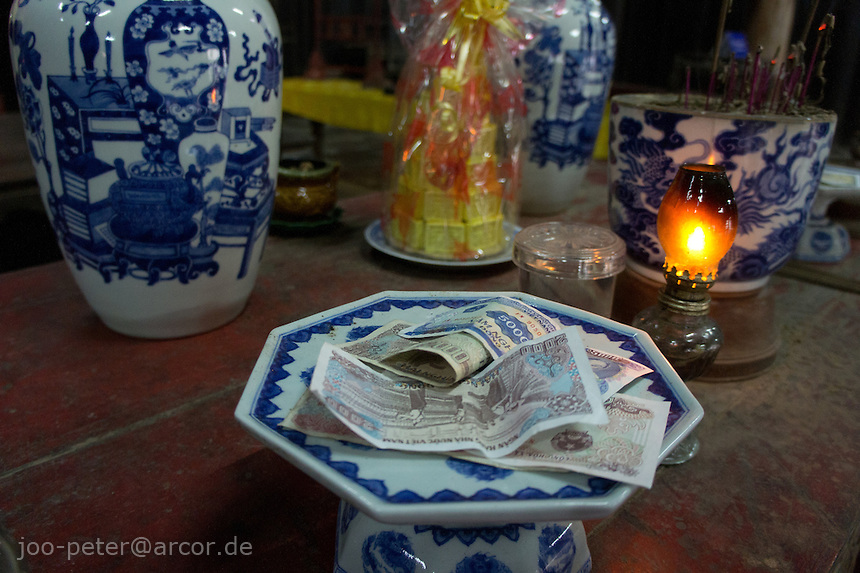 shrine in Tu Duc tomb with offerings (money bills) chinese porcelain good and petroleum lamp, city Hue, Vietnam. Vietnamese belief is a blend of Buddhism, Taoism and animism.