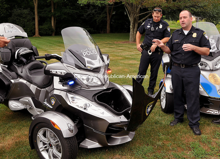 CHESHIRE, CT, 26 JULY 2011-072611JS02-- Cheshire Police officers Lt. Brian Pichnarcik, right, and officer Matthew Wium, left, show off the departments new three-wheeled Can-Am Spyder that is on loan for one year, during a press conference at the Cheshire Police Department on Tuesday. <br /> Jim Shannon/Republican-American
