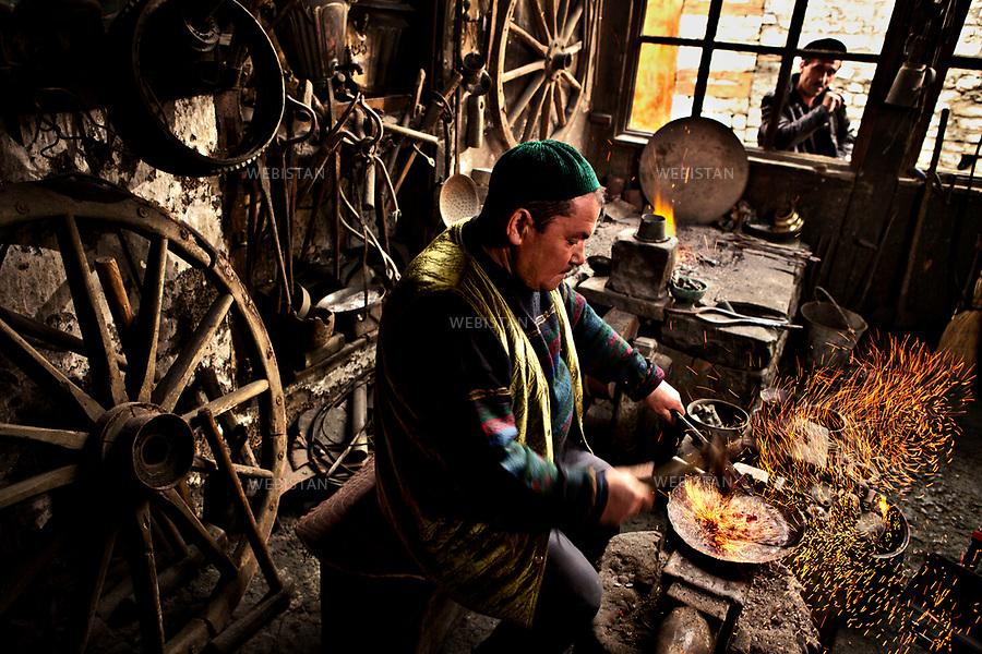 Azerbaijan, Shirvan, Ismailli (Ismayilli) District, Lahij (Lahic), April 17, 2012<br /> In his shop, a coppersmith heats and pounds copper to make a plate. Lahij is the old center of craftsmanship in Azerbaijan and was also the center of copper and arms production in the 18th and 19th centuries. Copper work historically has been the main source of income and the most popular job in Lahij. Today, this remote mountain village of about 2,000 residents has preserved its traditional way of life as well as the Lahiji language, which is only spoken. <br /> <br /> Azerba&iuml;djan, Chirvan, district de Ismayilli, Lahidj (Lahic), 17 avril 2012. <br /> Dans son atelier, un forgeron chauffe et bat du cuivre pour faire une plaque. Lahidj est un ancien centre artisanal de l&rsquo;Azerba&iuml;djan, au sein duquel le travail du cuivre est l&rsquo;une des principales sources de revenus et un m&eacute;tier tr&egrave;s populaire. Aux XVIIIe et XIXe si&egrave;cles, Lahidj &eacute;tait le centre de production du cuivre et d&rsquo;armes du pays. Le travail du cuivre a toujours &eacute;t&eacute; la principale source de revenus et d'emplois de Lahidj. Aujourd&rsquo;hui, ce village de montagne isol&eacute; d&rsquo;environ 2 000 habitants conserve un mode de vie traditionnel ainsi qu&rsquo;une langue orale, le lahidji.