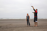 USA, Washington State, Long Beach Peninsula, International Kite Festival, Cameron Hendricks a young athletic boy stands by Kristian Robles who flies a power kite