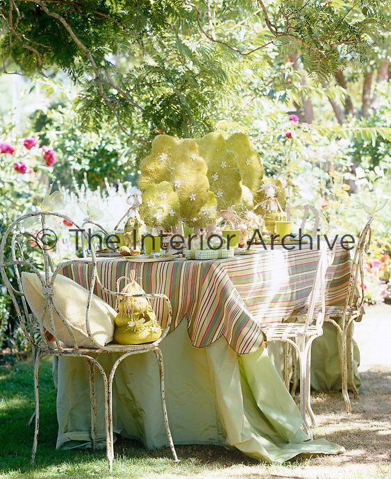 A table laid with presents and decorations for a child's summer party in an outdoor space