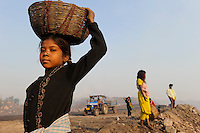 INDIA Jharkhand Dhanbad Jharia, children collect coal from dumping site of COAL INDIA coalfield to sell as coking coal on the market for the livelihood of her family, girl Sonia 8 years old / INDIEN Jharkand Dhanbad Jharia, Kinder sammeln Kohle auf einer Abraumhalde am Rande eines Kohletagebaus zum Verkauf als Koks auf dem Markt, Maedchen Sonia 8 Jahre, Hintergrund brennender Kohleabraum