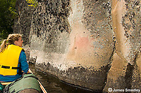 Young woman viewing pictographs from her canoe along the shore.