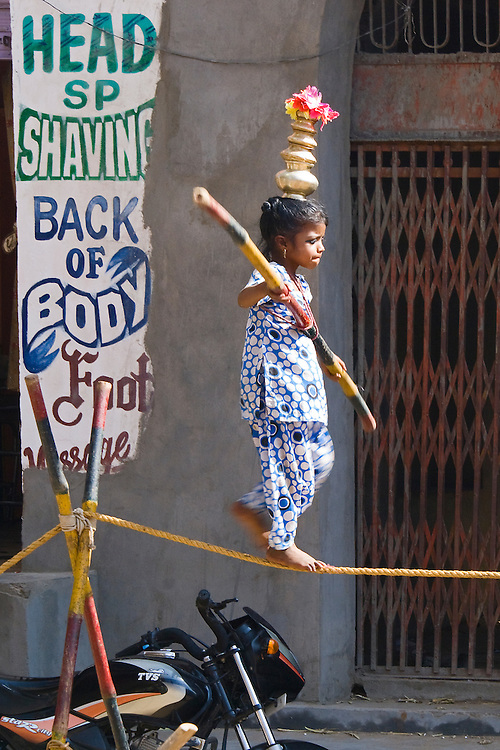 A young Indian Girl walks a tight rope strung between crossed bamboo rods like the one she carries for balance. The little girl is balancing a gold multi-tiered artifact topped by flowers on her head. Her brother went amongst the audience at the Pushkar Fair collecting coins iin a hat while her mother looked on.