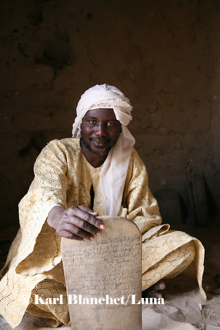 The marabout in his house in Timbuctu. Wooden boards around him are written with coranic versets that pupils need to know by heart. The coranic schools in Timbuctu are only open early in the morning and on Saturdays in order to allow pupils to attend the public school.