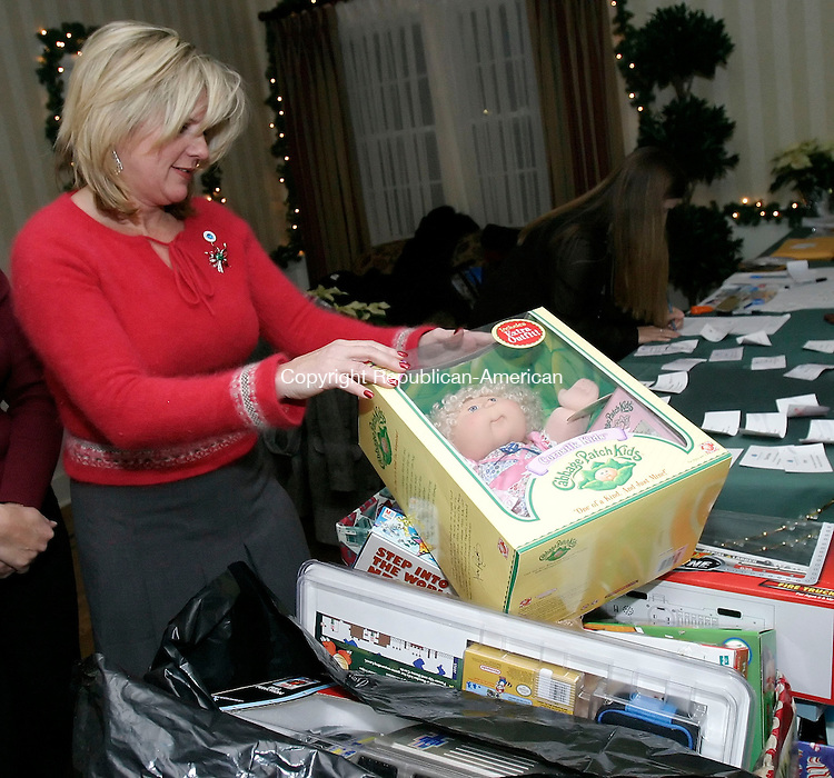 WATERBURY, CT 14 December 2005 -121405BZ13-<br /> Wendy Mutter, administrative assistant at the Waterbury Regional Chamber, places a Cabbage Patch Dollinto a pile of collected toys during the Waterbury Regional Chamber's annual holiday gathering at the Country Club of Waterbury Wednesday night.  Guests were asked to bring new, unwrapped toys for needy children.<br /> Jamison C. Bazinet Republican-American