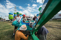 NWA Democrat-Gazette/ANTHONY REYES &bull; @NWATONYR<br /> Chris Adams, from left, Angel Ruiz, German Limon, David Aburto and Manuel Esteban, all with Pride Amusements of Joplin, build a dinosaur themed ride Monday, Sept. 28, 2015 for the Fall Carnival at Parsons Stadium in Springdale. Preperations for the carnival included setting up the rides, games and other boothes. The carnival begins Wednesday at 6 p.m. and continues until Oct. 4.