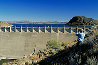 A man enjoys the fantastic view of Elephant Butte Dam through a pair of binoculars.  waterway, structure. New Mexico, Elephant Butte Dam.