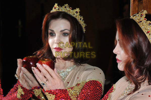 Priscilla Presley.Press launch to star in New Wimbledon Theatre's annual pantomime offering 'Snow White and the Seven Dwarfs' at The Savoy, Strand, London, England..September 26th, 2012.panto costume headshot portrait dress side profile mirror reflection hand apple gold red crown sequins sequined  .CAP/BF.©Bob Fidgeon/Capital Pictures.