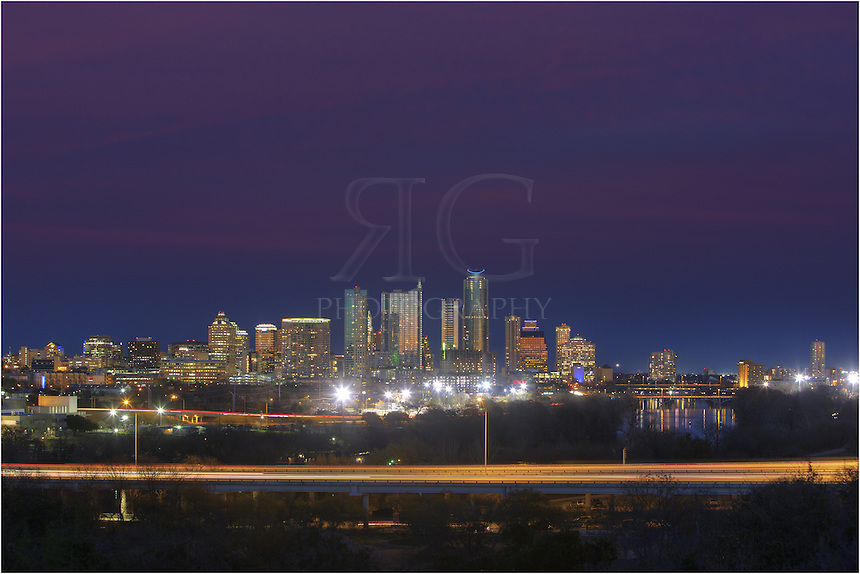 The evening view of the Austin Skyline from the  Zilker Clubhouse is not an image you will soon forget. On a peaceful February evening as the setting sun left traces of color in the sky, I captured this image of Austin with a telephoto lens...In the austin skyline, you can see prominent buidlings such as the Hyatt (on the right), the Austonian (middle, tallest), and the 360 Condos (to the left of the Austonian with a spire at the top). In the foreground, Mopac runs its loop around west Austin.