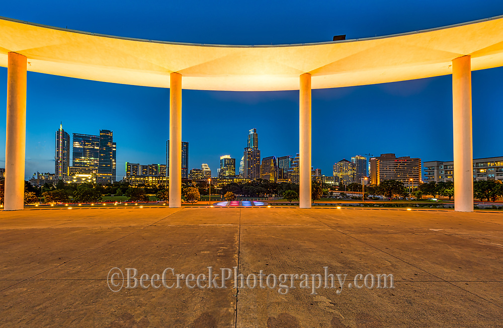 This is the Austin skyline through the pillars of the Long Center in downtown along Lady Bird Lake.  The long center for the performing art was name after Joe R. and Teresa Lozano Long who contributed 20 million dollar toward the project.  Becuase of cost the Long Center for the performing arts had to be completed in phases and it was officially completed after ten years in March 28 2008.  This is a favorite place for people to come and look at the Austin skyline.  We like the way the pillars frame up the city cityscape with the lighted pillars.  The Long Center used 95% of recycle material from the orginal Palmer Event Center to complete the phase 1 part of the project. Phase I of the building project included the Michael & Susan Dell Hall and the Debra & Kevin Rollins Studio Theatre. The building is a circular structure with a large pavillian with this beam around held up by pillars for very unique architecture.