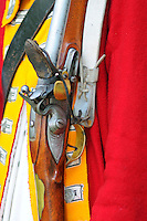 Reproduction Brown Bess shortland pattern flintlock musket, marked Grice 1762, rests at the shoulder of an infantryman of the 9th Regiment of Foot at a Revolutionary War encampment and muster, the Nathan Hale Homestead, Coventry, Connecticut, USA..