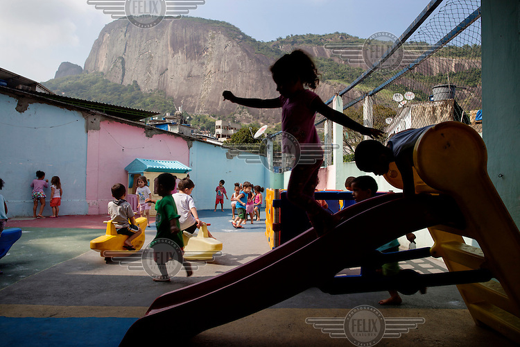 Children playing in a daycare centre in the Rocinha favela. In the background is the shere cliff face of the Dois Irmaos (Two Brothers Mountain).