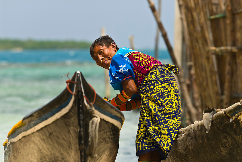 Kuna Indian woman wearing native costume with Mola embrodery with dugout canoes, Corbisky Island, San Blas Islands (Kuna Yala), Caribbean Sea, Panama