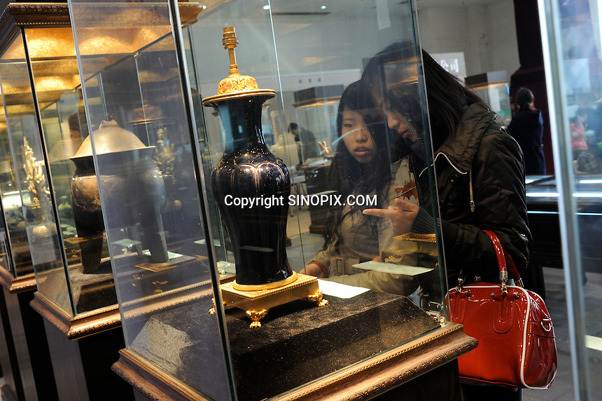 Buyers at the Hangzhou International Luxury Exhibition look at a Qing Dynasty vase for sale at 3.8 million RMB (350 thousand pounds) in Hangzhou, China 24 Jan 2010.<br /> <br /> PHOTOS BY SINOPIX