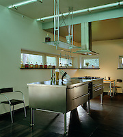 Free-standing stainless steel kitchen units are placed in the centre of the kitchen beneath an industrial extractor and a modern light suspended from the ceiling
