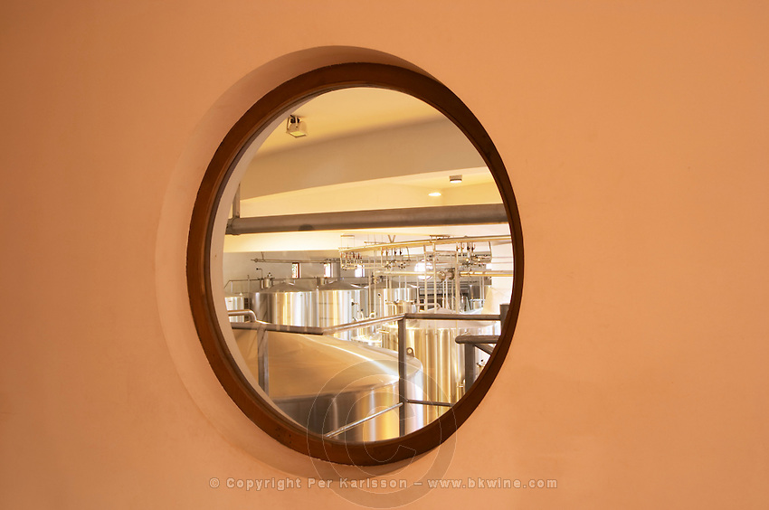 A view over the winery, and  stainless steel fermentation tanks in a round building through a round porthole type of window - Chateau Baron Pichon Longueville, Pauillac, Medoc, Bordeaux, Grand Cru