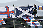 A Scottish fan stands proudly in front of a selection of Scottish and Faroese flags before the Euro 2008 group B qualifying match at the Svangaskard stadium in Toftir between the Faroe Islands and Scotland. The visitors won the match by 2 goals to nil to stay in contention for a place at the European football championships which were to be held in Switzerland and Austria in the Summer of 2008. It was the first time Scotland had won in the Faroes, the previous two matches ended in draws.