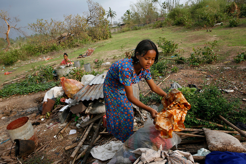 A Burmese girl picks through debris and the remains of her home destroyed by Cyclone Nargis in Thanlyin, Burma, May 9, 2008.