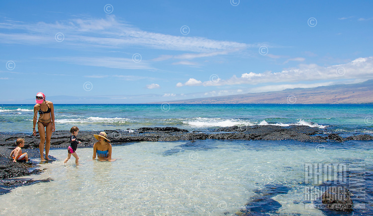 Two mothers with their children enjoy the tidal pools at a beach in Puako, South Kohala, Big Island.