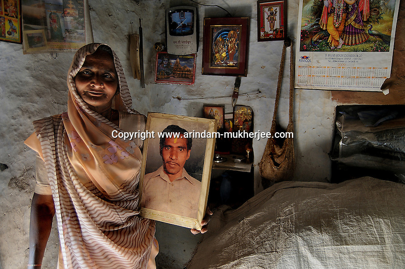 Geeta Bai is standing in her house with a photograph of her husband. Geeta Bai is working with Sadhna for last 11 years. When her husband died she had to take up the work with Sadhna. She stays alone in her mud hut at sheesvi village. Though her son is well established in Udaipur she likes her independence. She doesn't even take any kind of help from her children. She said Sadhna gave her a new way of life. Udaipur, Rajasthan, India. 25.1. 2011. Arindam Mukherjee.