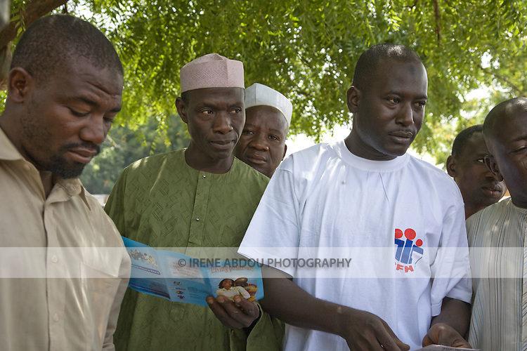 A Society for Family Health (SFH)-trained HIV/AIDS prevention volunteer talks to men in Yankaba market in Kano, Nigeria, HIV counseling and testing services.  The   Society for Family Health (SFH) is Nigeria's largest indigenous non-profit and affiliate of the international social marketing organization, Population Services International (PSI).
