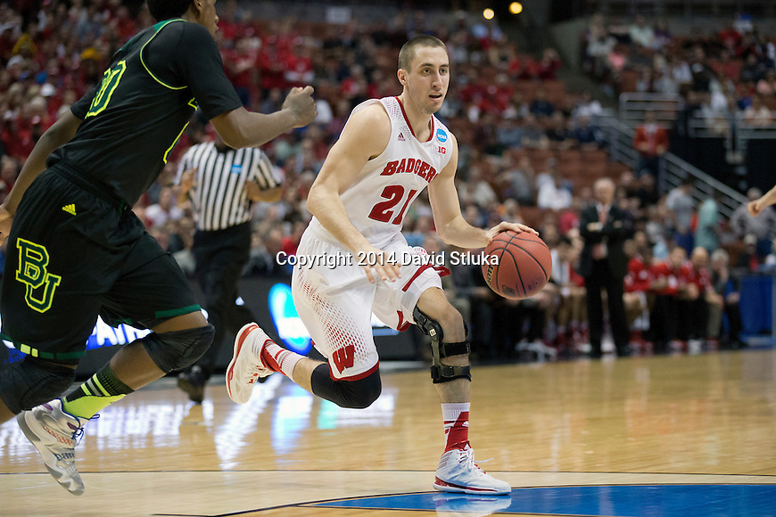 Wisconsin Badgers guard Josh Gasser (21) handles the ball during the fourth-round game in the NCAA college basketball tournament against the Baylor Bears Thursday, March 27, 2014 in Anaheim, California. The Badgers won 69-52. (Photo by David Stluka)