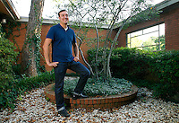 NWA Democrat-Gazette/DAVID GOTTSCHALK  Dustin Bartholomew stands Thursday, September 10, 2015 in his favorite personal space, the front courtyard at his home in Fayetteville.