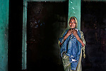Jomira Khatun holds her son Aynal's (26) jacket while posing for a portrait in front of the living room, which Aynal died when the Tazreen Fashions factory fire swept through surrounding buildings in Ashulia, Bangladesh.