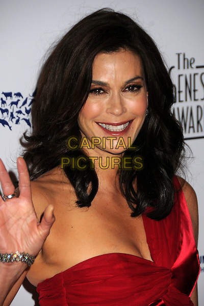TERI HATCHER.24th Annual Genesis Awards - Arrivals held at the Beverly Hilton Hotel, Beverly Hills, California, USA, 20th March 2010..portrait headshot smiling make-up red one shoulder wrinkles hand waving .CAP/ADM/BP.©Byron Purvis/AdMedia/Capital Pictures.