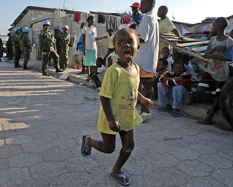 Earthquake aftermath in Haiti on Sunday, January 24, 2010..The Brazilian Battalion and and the US Army in Cite Soleil join for a food distribution on Sunday morning. A child runs to get in line to get food.