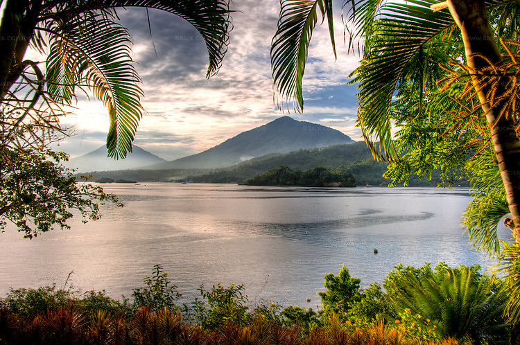Tropical trees and carefully manicured shrubs frame the view of the Lembeh Strait and North Sulawesi in the late afternoon.  (The Lembeh Resort, HDR image)