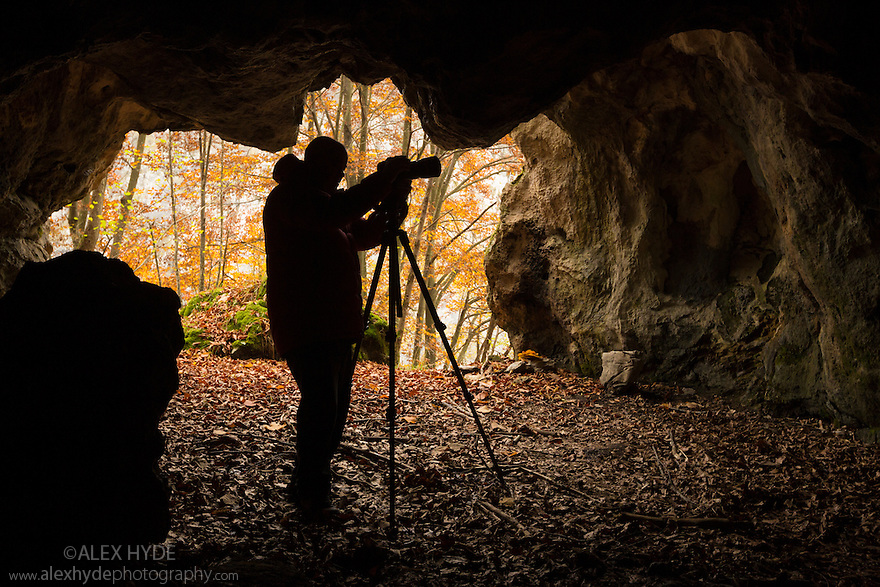 Photographer silhouetted in entrance of limestone cave, Plitvice Lakes National Park, Croatia. November.