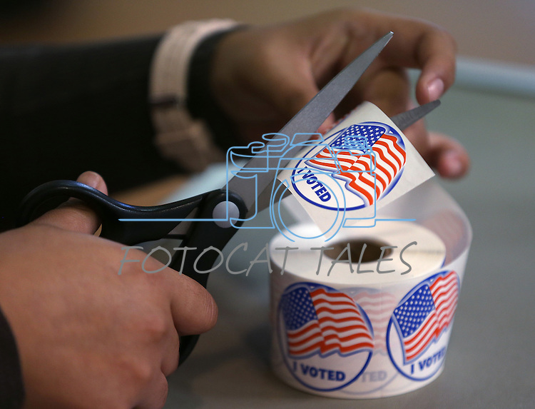 A volunteer hands out stickers to voters in Carson City, Nev., on Tuesday, Nov. 4, 2014. (AP Photo/Cathleen Allison)