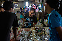 Bali, Indonesia.  Potential Customer Inspecting the Fish,  Jimbaran Fish Market.