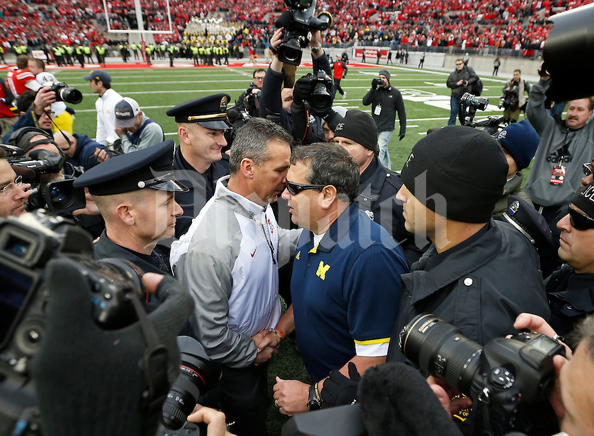 Ohio State Buckeyes head coach Urban Meyer shakes hands with Michigan Wolverines head coach Brady Hoke following the NCAA football game at Ohio Stadium on Nov. 29, 2014. The Buckeyes won 42-28. (Adam Cairns / The Columbus Dispatch)