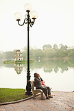 VIETNAM, Hanoi, a woman sits on a bench early in the morning, Hoan Kiem Lake