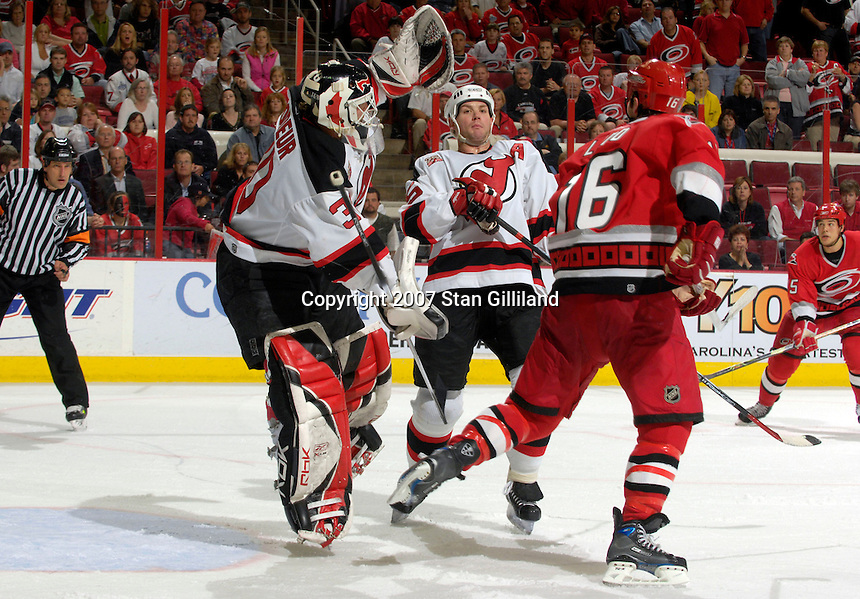 Carolina Hurricanes' Andrew Ladd watches as the New Jersey Devils' goalie Martin Brodeur attempts to catch a puck Thursday, March 15, 2007 at the RBC Center in Raleigh, NC. Also pictured is the Devils' Jamie Langenbrunner. New Jersey won 3-2.