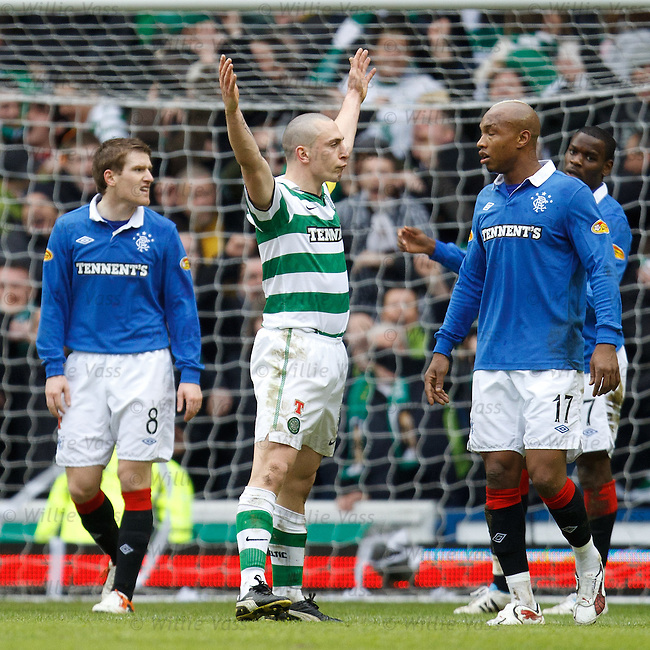 Scott Brown celebrates his goal for Celtic as the Rangers players stand dejected